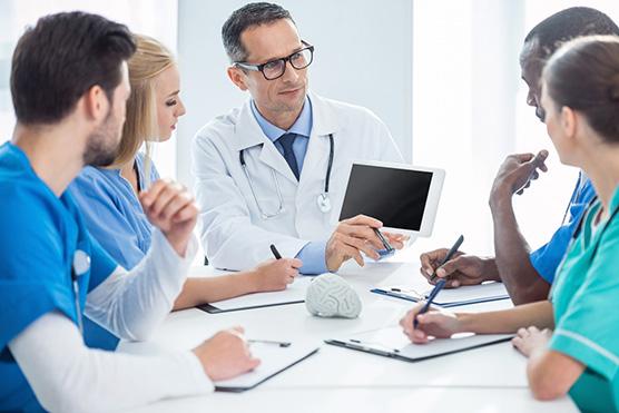 team of focused doctors having conversation and looking at digital tablet